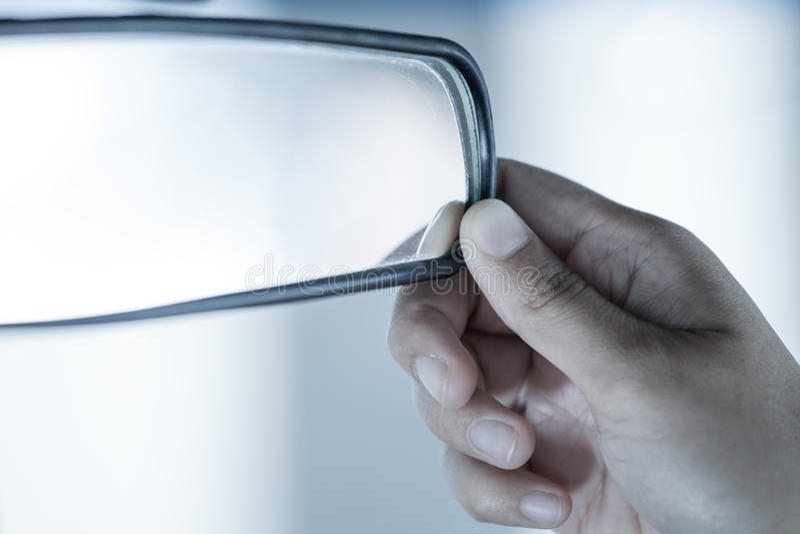 Χέρια γυναικών που ρυθμίζουν τον οπισθοσκόπο καθρέφτη στο αυτοκίνητο στοκ εικόνα με δικαίωμα ελεύθερης χρήσης