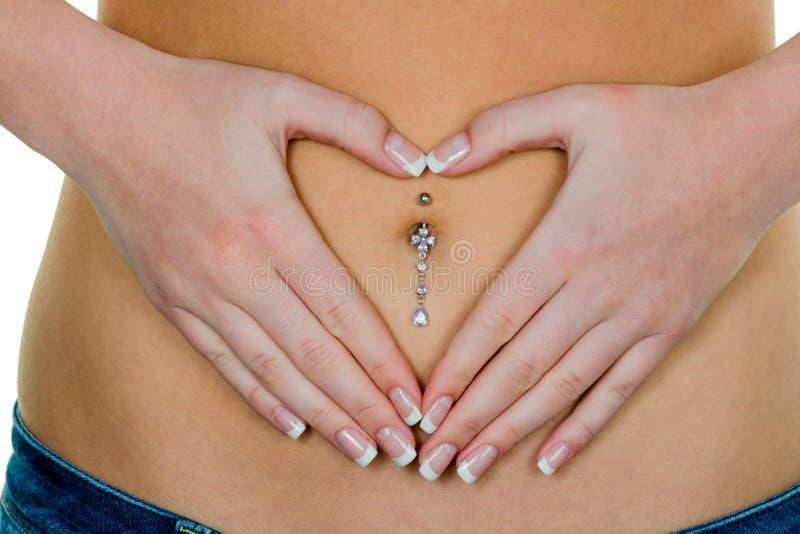 Χέρια γυναικών στο στομάχι στοκ εικόνα