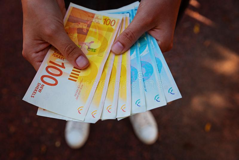 Χέρια γυναικών ` s δύο που κρατούν έναν ανεμιστήρα των χρημάτων των ισραηλινών νέων Shekel στοκ φωτογραφία