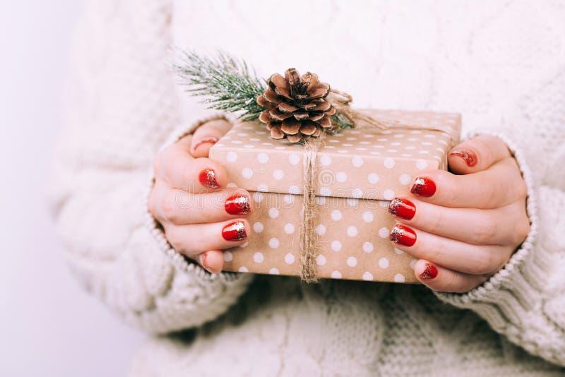 Χέρια γυναικών ` s με το κιβώτιο δώρων Χριστουγέννων στοκ εικόνες