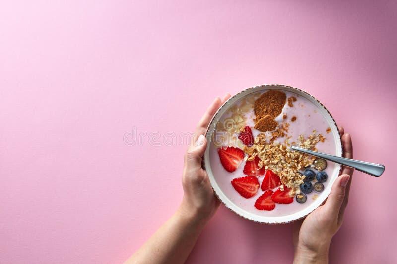 Χέρια γυναικών ` s που κρατούν ένα κύπελλο του οργανικού καταφερτζή γιαουρτιού με τις φράουλες, την μπανάνα, το βακκίνιο, τις νιφ στοκ φωτογραφία