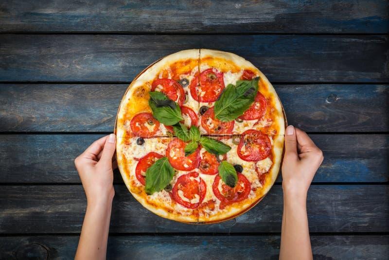 Χέρια γυναικών ` s που κρατούν μια τέλεια πίτσα Μαργαρίτα με τις φέτες ντοματών, τις ελιές και τα φύλλα βασιλικού Τοπ όψη στοκ φωτογραφίες