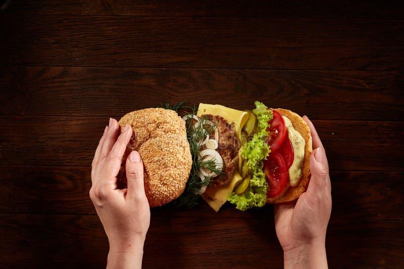Χέρια γυναικών ` s που κρατούν παραδοσιακό αμερικανικό burger στο ξύλινο υπόβαθρο, τοπ άποψη, κινηματογράφηση σε πρώτο πλάνο στοκ φωτογραφία με δικαίωμα ελεύθερης χρήσης