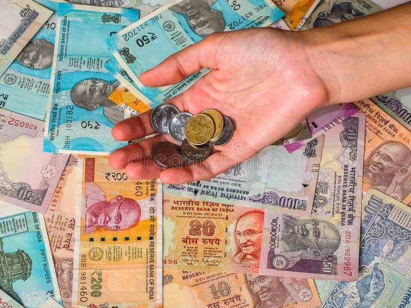 Χέρια γυναικών ` s που κρατούν τα νομίσματα άνω των 10, 20, 50, 100, 200, 500 και 2000 ινδικών ρουπίων στοκ φωτογραφίες με δικαίωμα ελεύθερης χρήσης