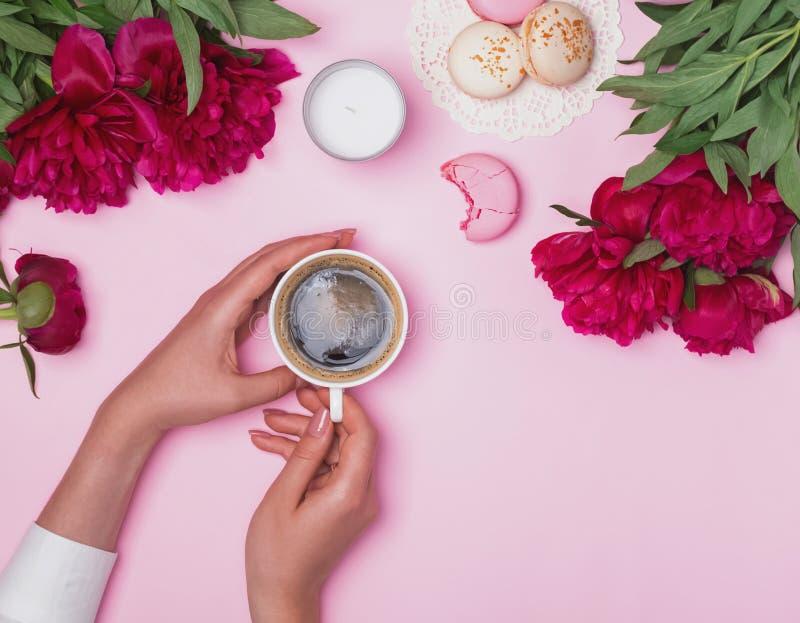Χέρια γυναικών ` s που κρατούν τον καφέ στον πίνακα με τα peonies και macarons στοκ φωτογραφίες