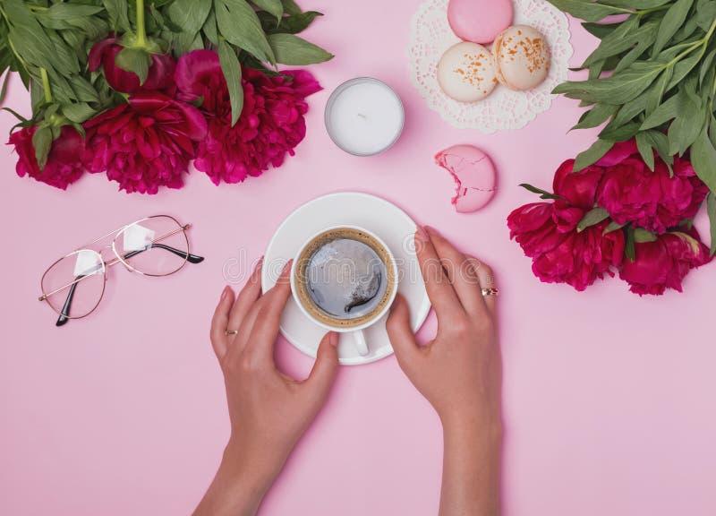 Χέρια γυναικών ` s που κρατούν τον καφέ στον πίνακα με τα peonies και macarons στοκ εικόνα