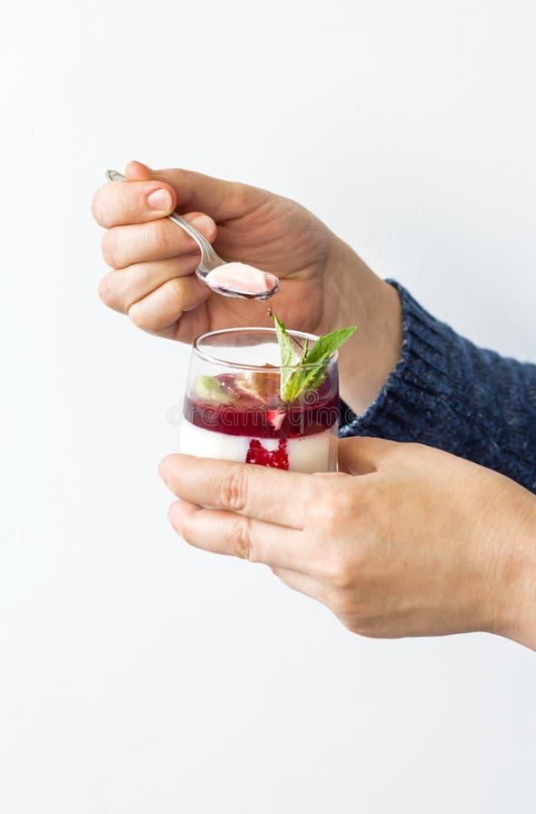 Χέρια γυναικών ` s που κρατούν το κουτάλι και το επιδόρπιο στοκ φωτογραφία