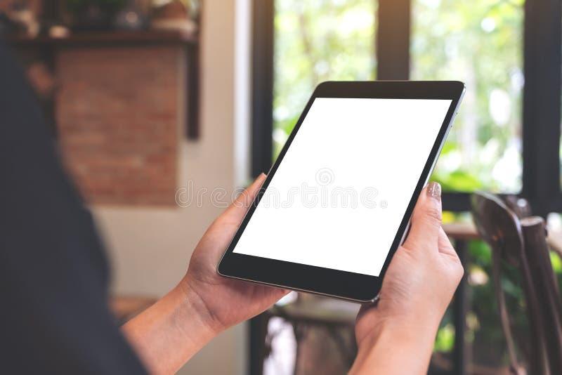 Χέρια γυναικών ` s που κρατούν το μαύρο PC ταμπλετών με την κενή οθόνη υπολογιστών γραφείου στον καφέ στοκ εικόνα