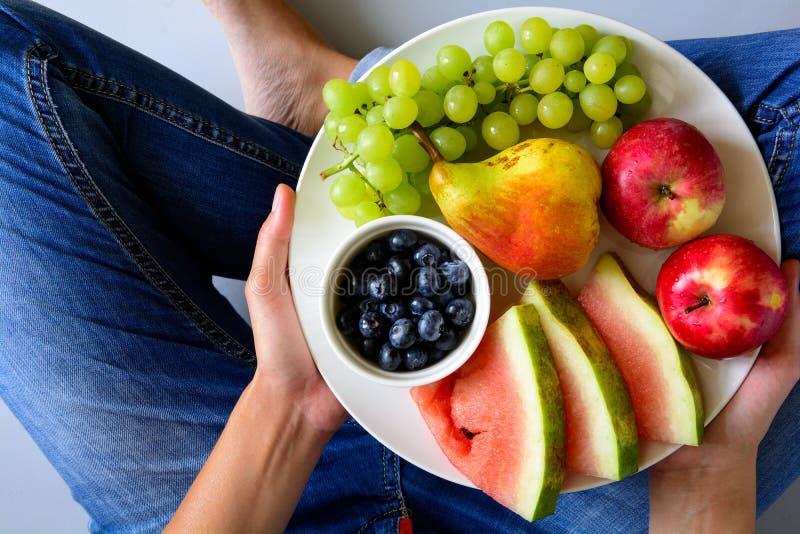 Χέρια γυναικών ` s που κρατούν το πιάτο με τα θερινά φρούτα: καρπούζι, βακκίνιο, μήλα, αχλάδι και σταφύλι στο άσπρο πιάτο στοκ εικόνα