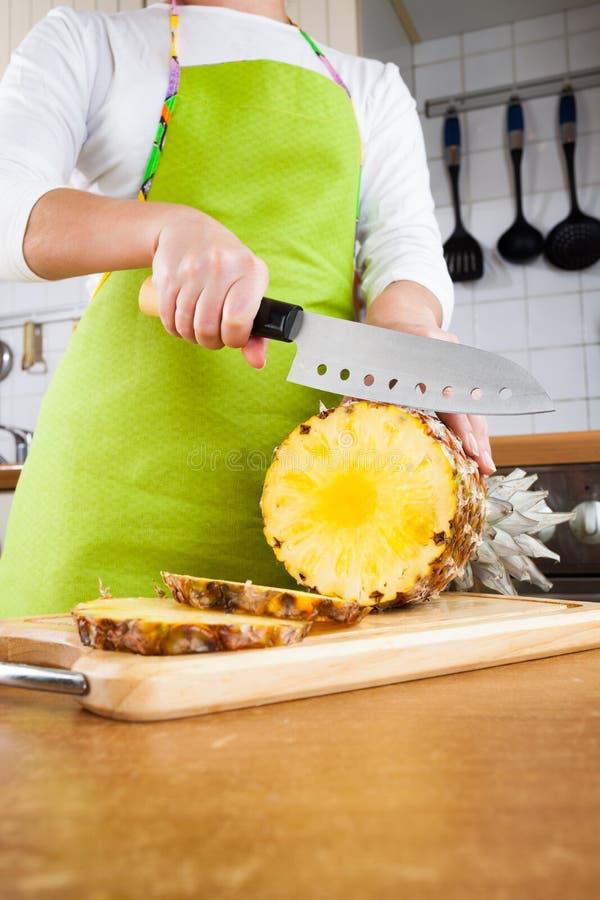 Χέρια γυναικών ` s που κόβουν τον ανανά στοκ φωτογραφία με δικαίωμα ελεύθερης χρήσης