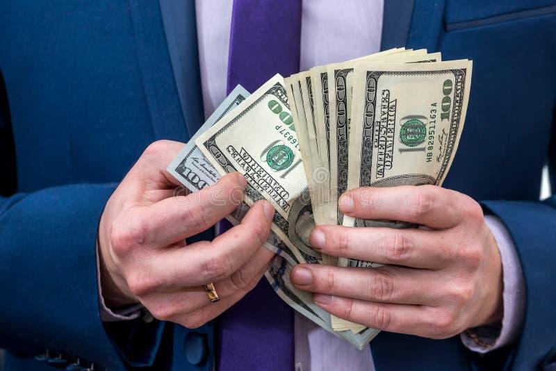 Χέρια διευθυντή που μετρούν τα τραπεζογραμμάτια δολαρίων στοκ φωτογραφία