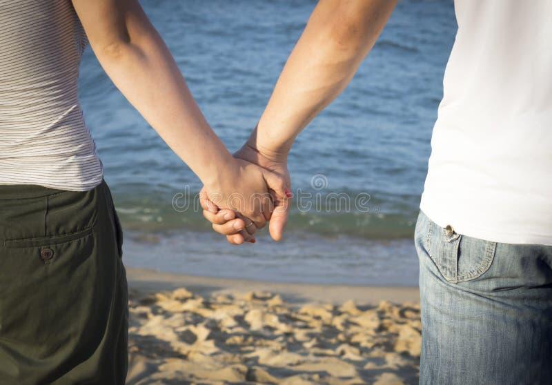 Χέρια εκμετάλλευσης ανδρών και γυναικών ενάντια στη θάλασσα στοκ φωτογραφία