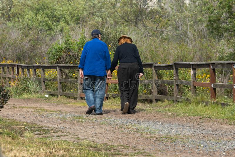 Χέρια εκμετάλλευσης ζεύγους που περπατούν μακριά στοκ φωτογραφίες
