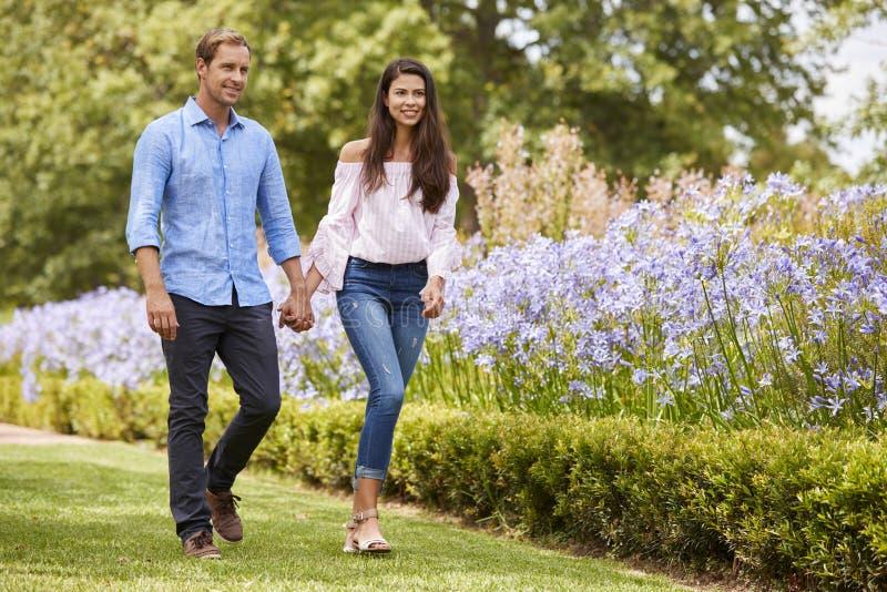 Χέρια εκμετάλλευσης ζεύγους στο ρομαντικό περίπατο στο πάρκο από κοινού στοκ φωτογραφίες