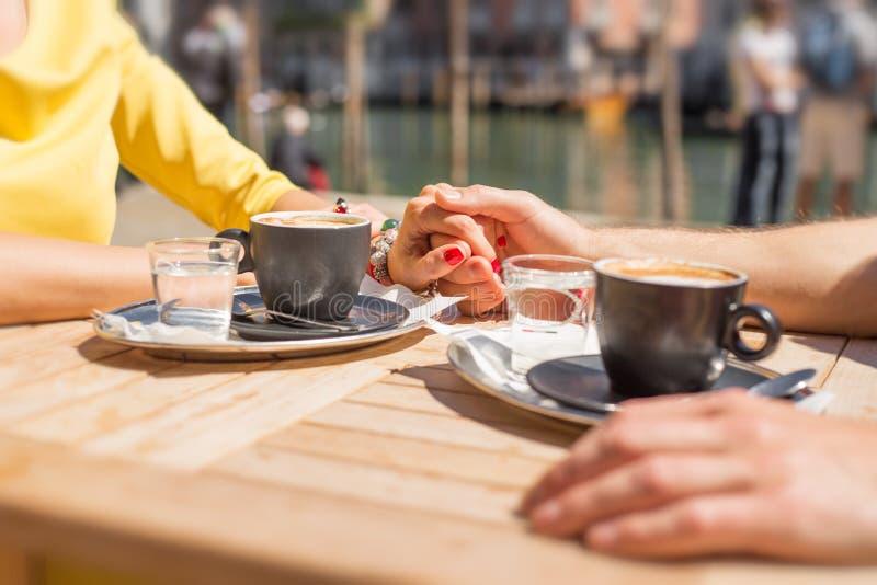 Χέρια εκμετάλλευσης ζεύγους και καφές κατανάλωσης στον καφέ υπαίθρια στοκ εικόνες με δικαίωμα ελεύθερης χρήσης