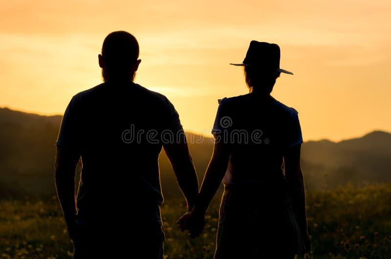 Χέρια εκμετάλλευσης ζεύγους και προσοχή του ηλιοβασιλέματος, σκιαγραφία στοκ εικόνα