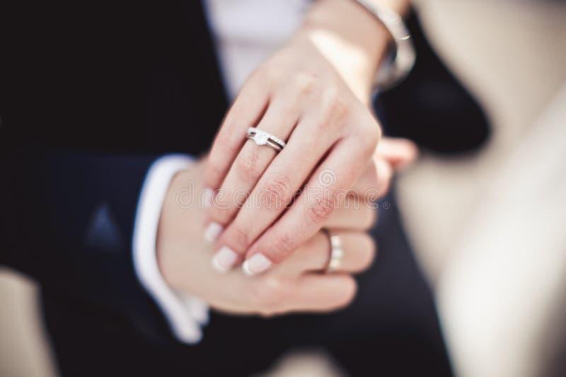 Χέρια εκμετάλλευσης με τα γαμήλια δαχτυλίδια στοκ φωτογραφία με δικαίωμα ελεύθερης χρήσης