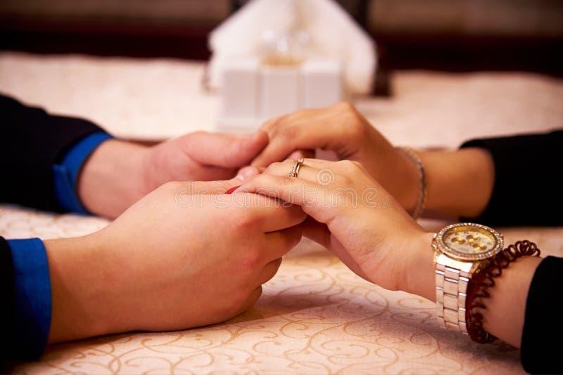 Χέρια ενός αγαπώντας ζεύγους για έναν πίνακα σε μια κινηματογράφηση σε πρώτο πλάνο εστιατορίων στοκ εικόνες