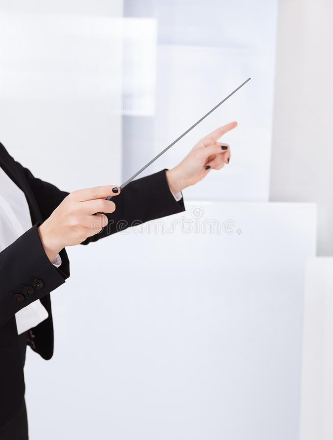 Χέρια ενός αγωγού μουσικής με ένα μπαστούνι στοκ εικόνα