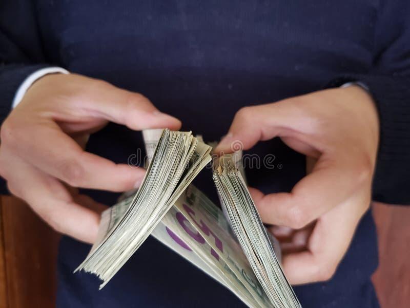 χέρια ενός ατόμου που κρατά τα αμερικανικά τραπεζογραμμάτια δολαρίων στοκ φωτογραφία με δικαίωμα ελεύθερης χρήσης