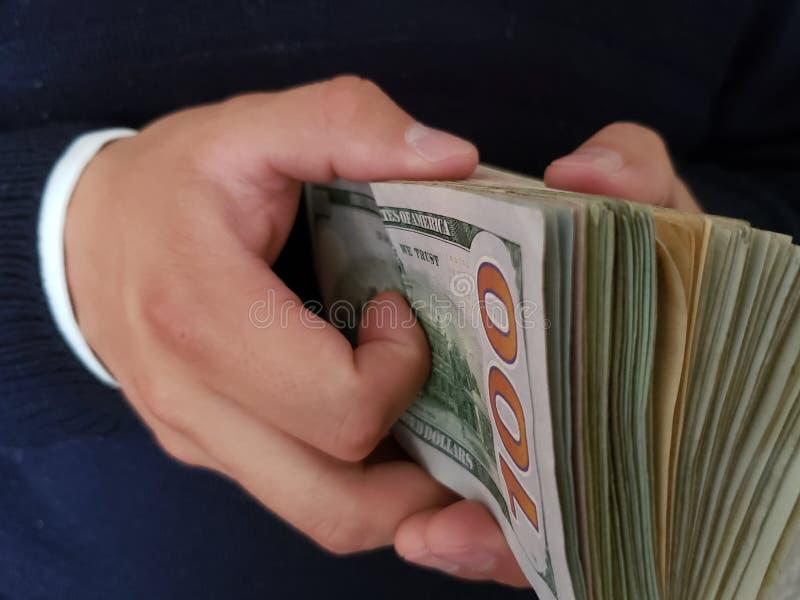 χέρια ενός ατόμου που κρατά τα αμερικανικά τραπεζογραμμάτια δολαρίων στοκ φωτογραφίες με δικαίωμα ελεύθερης χρήσης