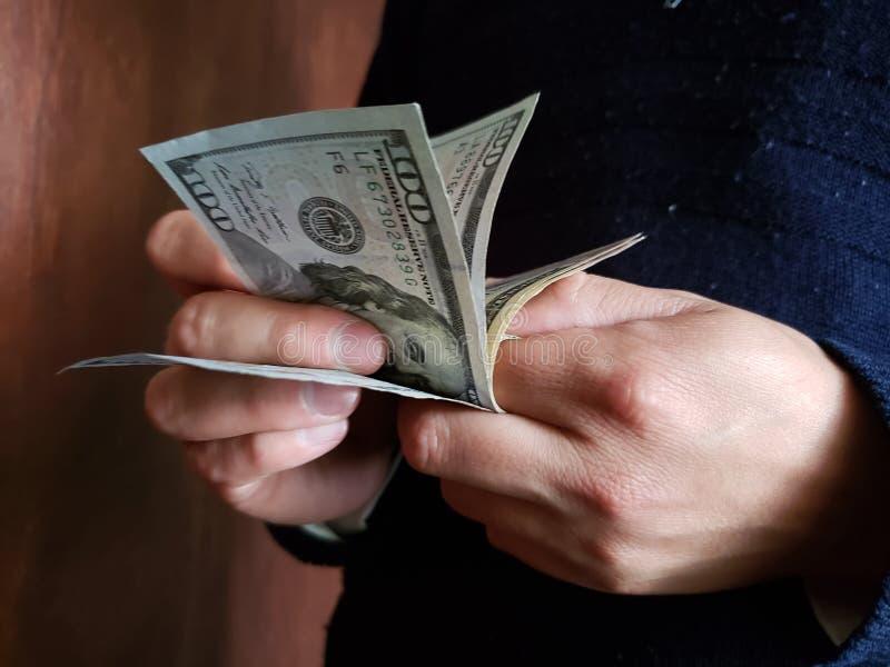 χέρια ενός ατόμου που μετρά τα αμερικανικά τραπεζογραμμάτια δολαρίων στοκ εικόνες