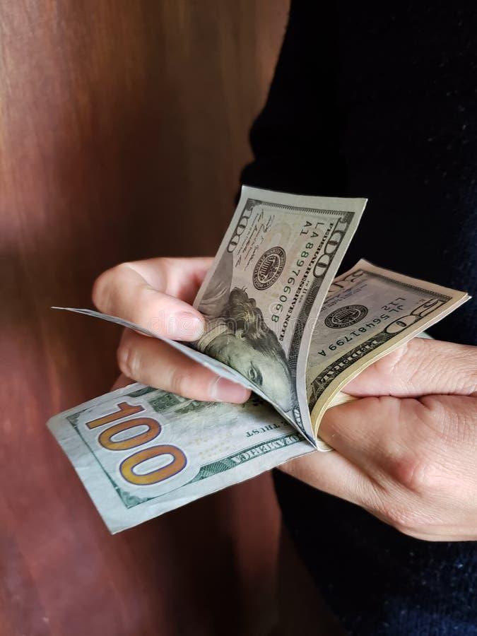 χέρια ενός ατόμου που μετρά τα αμερικανικά τραπεζογραμμάτια δολαρίων στοκ εικόνα