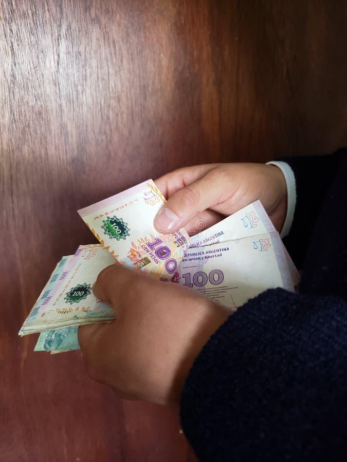 χέρια ενός ατόμου που μετρά τα αργεντινά τραπεζογραμμάτια στοκ φωτογραφία
