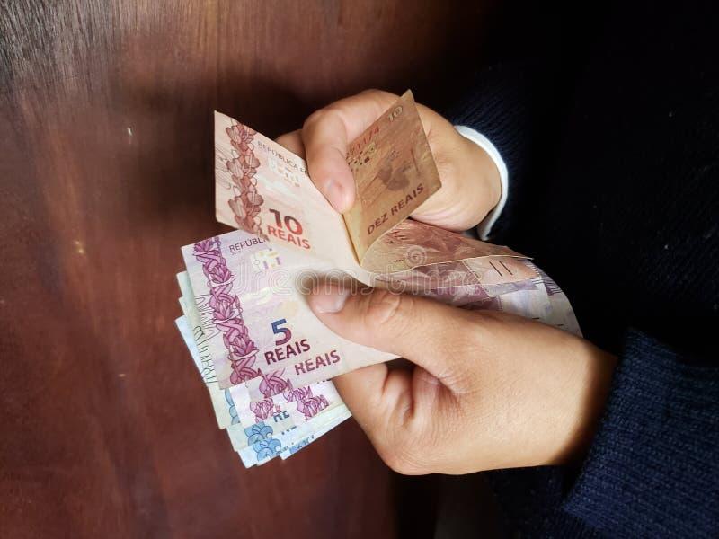 χέρια ενός ατόμου που μετρά τα βραζιλιάνα τραπεζογραμμάτια στοκ εικόνες με δικαίωμα ελεύθερης χρήσης