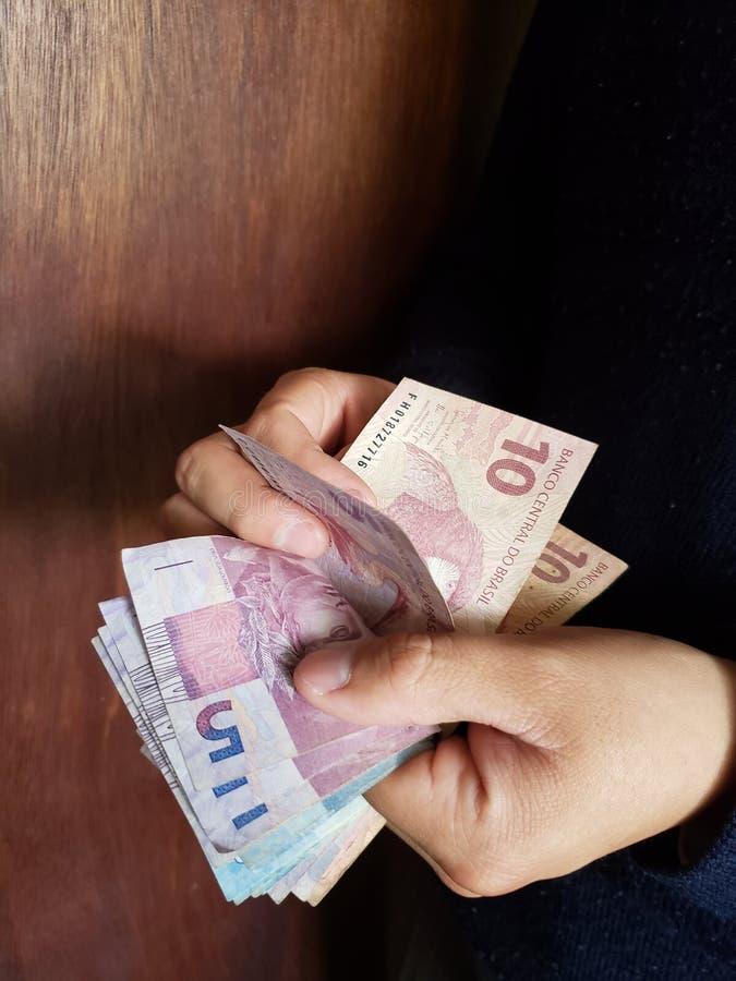χέρια ενός ατόμου που μετρά τα βραζιλιάνα τραπεζογραμμάτια στοκ φωτογραφία με δικαίωμα ελεύθερης χρήσης