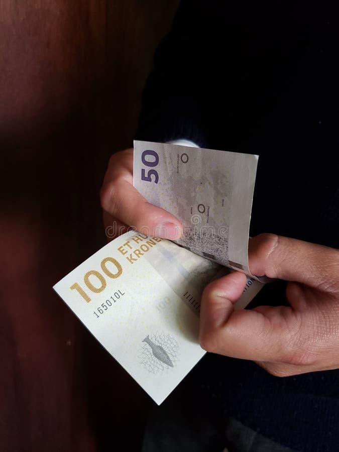 χέρια ενός ατόμου που μετρά τα δανικά τραπεζογραμμάτια στοκ φωτογραφία