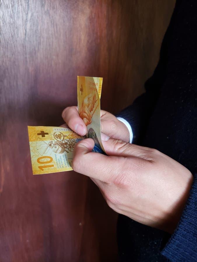 χέρια ενός ατόμου που μετρά τα ελβετικά τραπεζογραμμάτια στοκ εικόνες