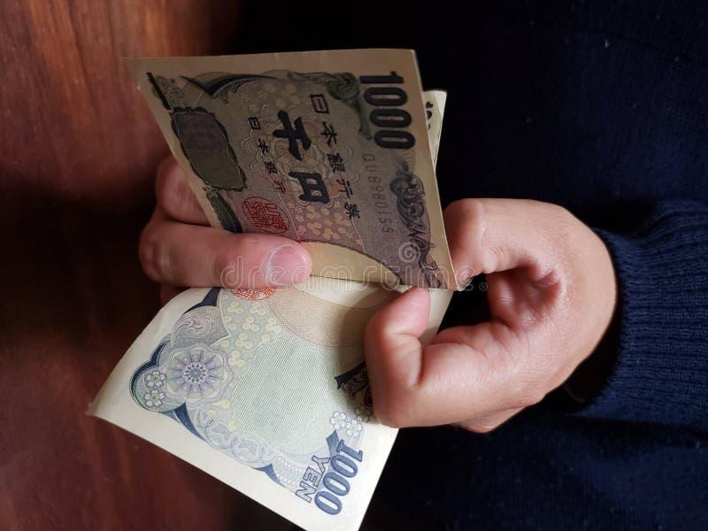 χέρια ενός ατόμου που μετρά τα ιαπωνικά τραπεζογραμμάτια στοκ εικόνες