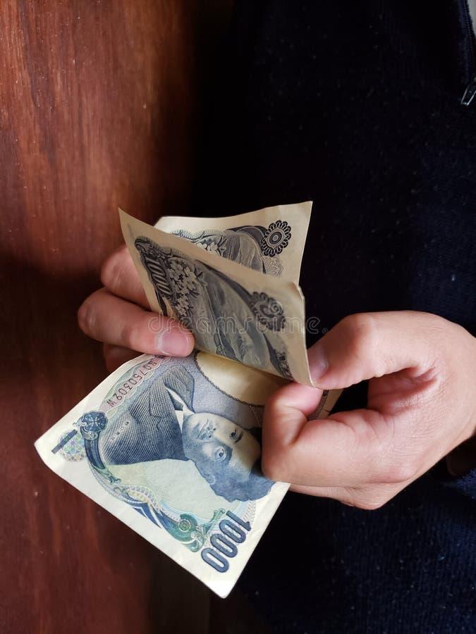 χέρια ενός ατόμου που μετρά τα ιαπωνικά τραπεζογραμμάτια στοκ εικόνα