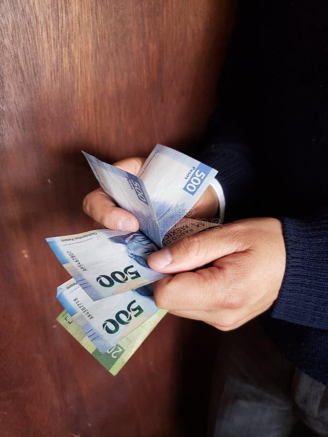 χέρια ενός ατόμου που μετρά τα μεξικάνικα τραπεζογραμμάτια στοκ φωτογραφίες