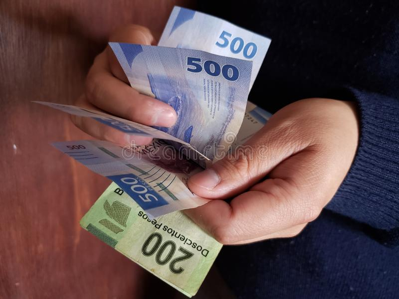 χέρια ενός ατόμου που μετρά τα μεξικάνικα τραπεζογραμμάτια στοκ φωτογραφία με δικαίωμα ελεύθερης χρήσης