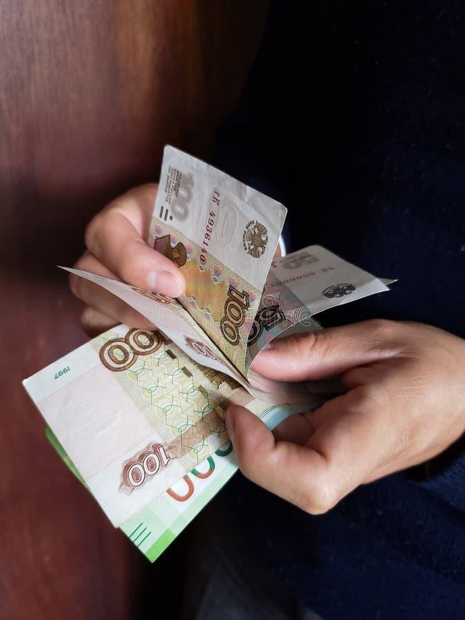 χέρια ενός ατόμου που μετρά τα ρωσικά τραπεζογραμμάτια στοκ φωτογραφία