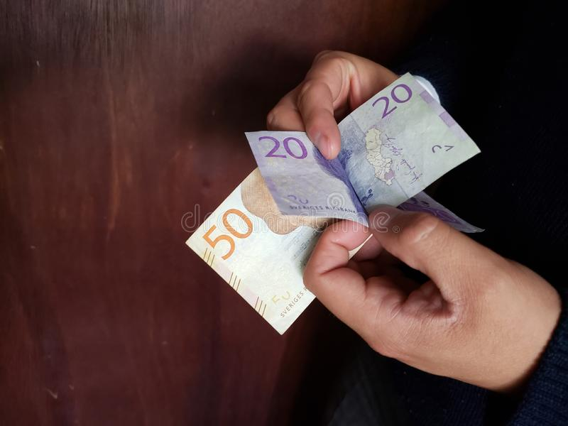 χέρια ενός ατόμου που μετρά τα σουηδικά τραπεζογραμμάτια στοκ εικόνες