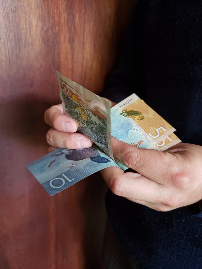 χέρια ενός ατόμου που μετρά τα τραπεζογραμμάτια της Νέας Ζηλανδίας στοκ εικόνες