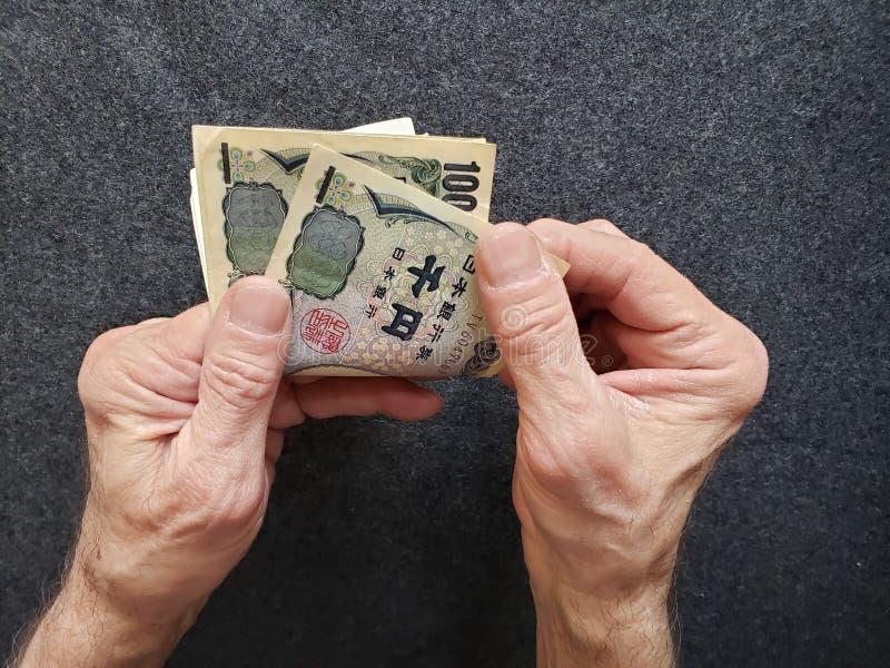 χέρια ενός ηληκιωμένου που μετρά τα ιαπωνικά τραπεζογραμμάτια στοκ φωτογραφία