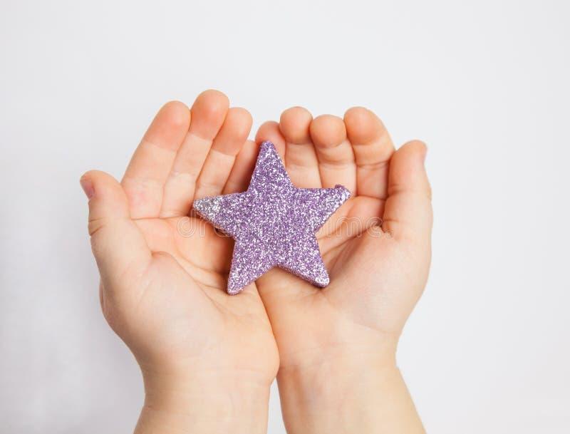 Χέρια ενός παιδιού που κρατά το μικρό αστέρι στοκ εικόνα με δικαίωμα ελεύθερης χρήσης