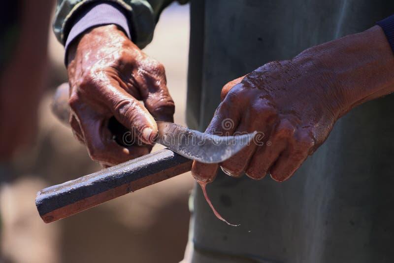 Χέρια ενός ψαρά με ένα μαχαίρι στοκ εικόνα με δικαίωμα ελεύθερης χρήσης