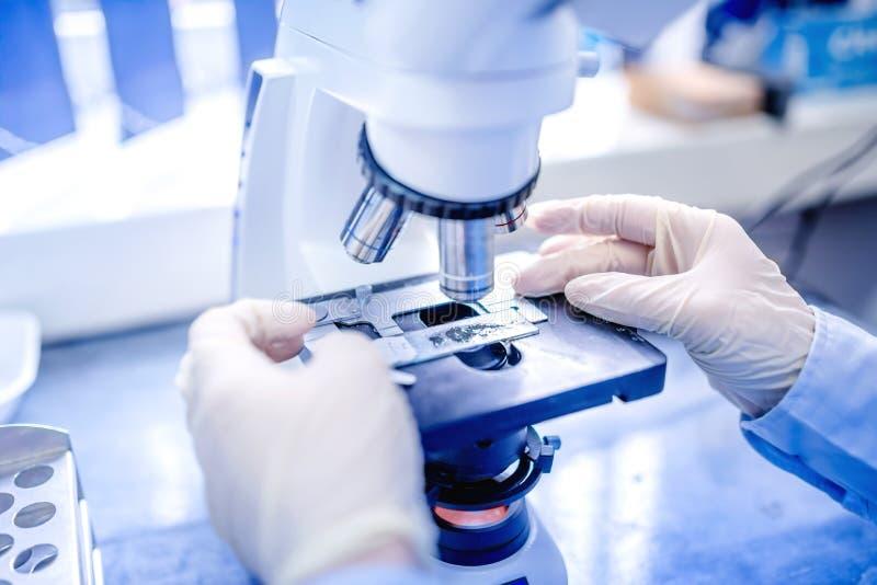 Χέρια επιστημόνων με το μικροσκόπιο, εξετάζοντας τα δείγματα και το υγρό Ιατρική έρευνα με τον τεχνικό εξοπλισμό στοκ φωτογραφίες