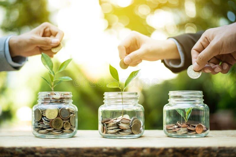 Χέρια επιχειρηματιών που βάζουν το νόμισμα χρημάτων στο βάζο γυαλιού στοκ φωτογραφία
