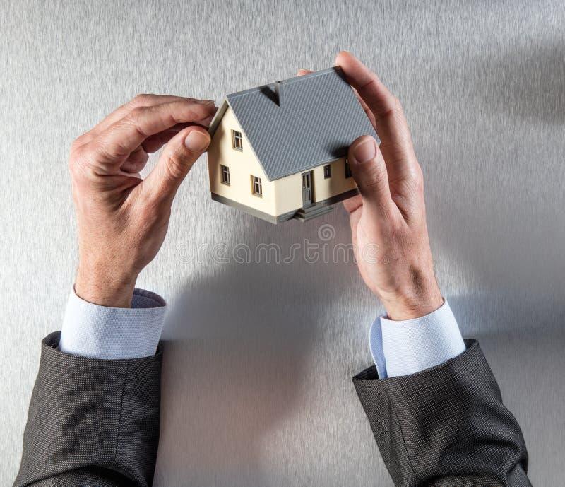 Χέρια επιχειρηματιών που εξετάζουν τη στέγη για την αξιολόγηση ή τη μόνωση σπιτιών στοκ εικόνες