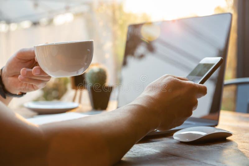 Χέρια επιχειρηματιών που κρατούν το φλυτζάνι καφέ και το τηλέφωνο κυττάρων με το lap-top στον πίνακα στοκ φωτογραφία με δικαίωμα ελεύθερης χρήσης