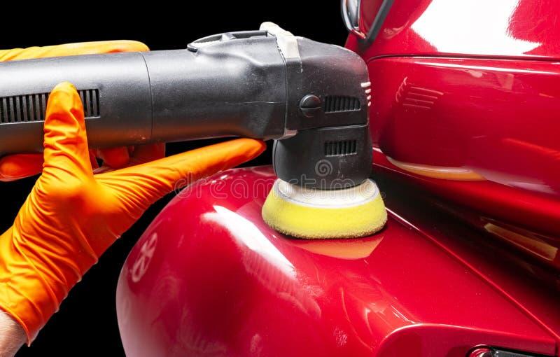 Χέρια εργαζομένων κεριών στιλβωτικής ουσίας αυτοκινήτων που εφαρμόζουν την προστατευτική ταινία πρίν γυαλίζει Buffing και στίλβωσ στοκ εικόνα με δικαίωμα ελεύθερης χρήσης