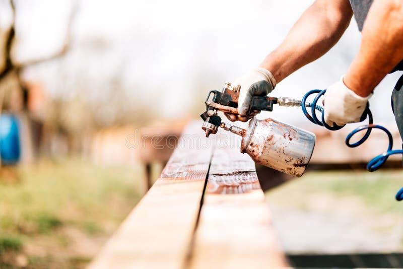 χέρια εργαζομένων που χρησιμοποιούν airbrush και πυροβόλο όπλο ψεκασμού για τη ζωγραφική της ξυλείας στοκ εικόνα