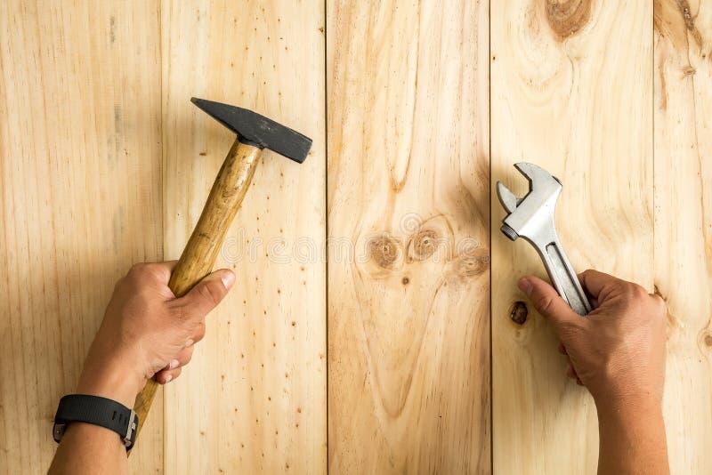 Χέρια εργαζομένων ` s που κρατούν το γαλλικό κλειδί σφυριών και πιθήκων έτοιμο να καθορίσει κάτι στοκ εικόνα με δικαίωμα ελεύθερης χρήσης