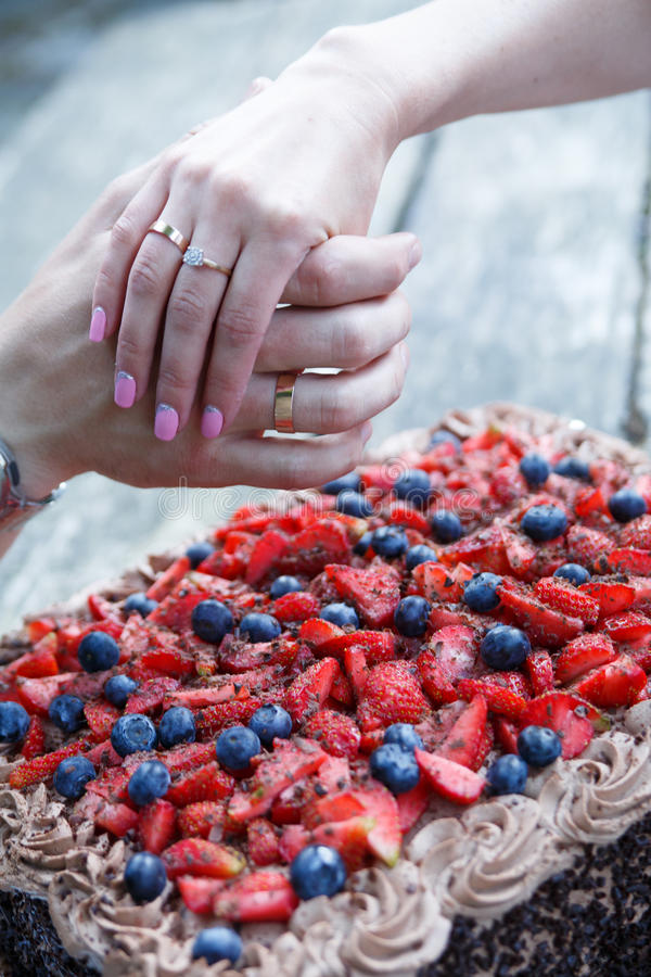Χέρια ζεύγους με το γαμήλιο δαχτυλίδι και κέικ σοκολάτας με τα μούρα στοκ φωτογραφία με δικαίωμα ελεύθερης χρήσης